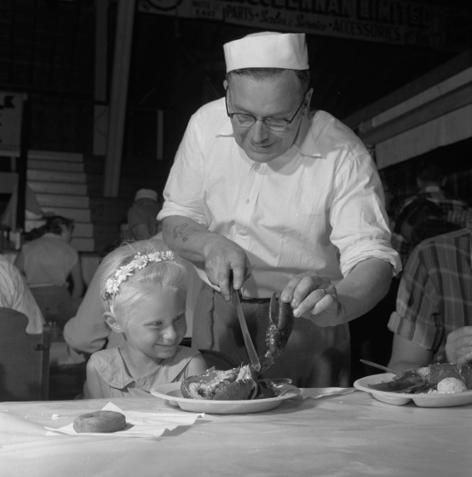 A black-and-white photograph of a man helping a little girl sitting at a table with her lobster meal.