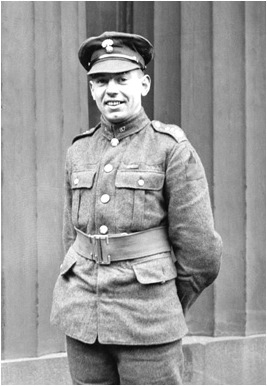 A black-and-white photograph of a smiling soldier standing with his arms behind his back.