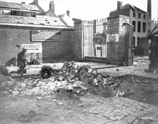 A black-and-white photograph of a town with damaged buildings, with stone and rubble heaped in the middle. One soldier is bent to the ground beside a large pile of debris. A nearby soldier standing to the left is watching him.