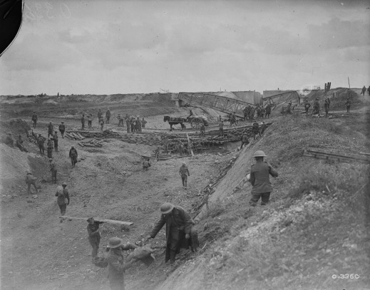 A black-and-white photograph of a dried-out canal with a crooked bridge in the background. A bridge in the middle distance has a horse-drawn carriage crossing it with supplies. Throughout the photo, soldiers are moving about, and some are carrying supplies.