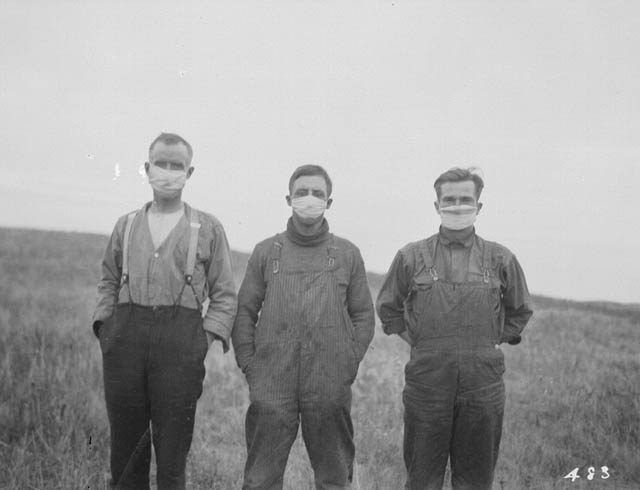 Black-and-white photo of three men wearing hygienic masks.