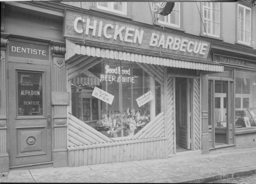 "A black-and-white photograph of the exterior of Nick's Chicken Barbecue restaurant. A neon sign in the window advertises ""Good Food"" and ""Beer & Wine""."