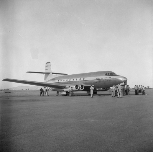 A black-and-white photograph of an airplane on a runway with groups of men hanging around the aircraft.