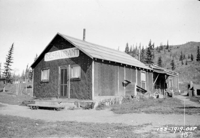 A black-and-white photograph of the exterior of a restaurant located on a dirt road in a remote area.