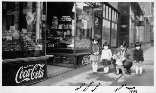 A black-and-white photograph showing a Japanese-Canadian man, who is crouching, and four children in front of a store.