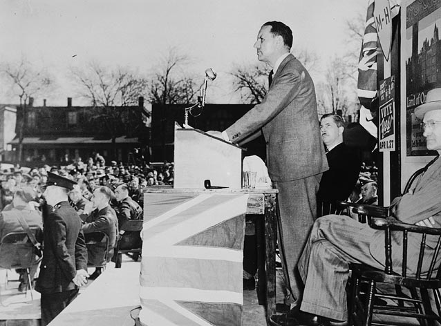 A black-and-white photograph of a man standing at a lectern that is wrapped in the Union Jack, in front of a large audience of workers. Policemen are in the first row.