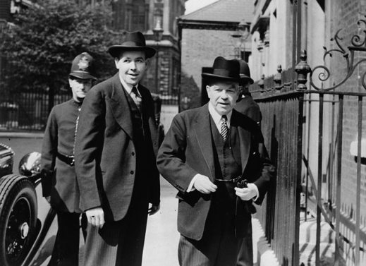 A black-and-white photograph of two men standing near a tall, iron gate. A London bobby (police officer) is visible behind them.