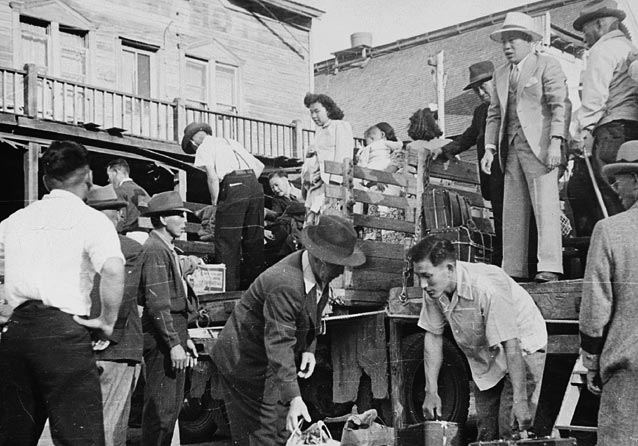 A black-and-white photograph showing twelve Japanese Canadians unloading a truck.