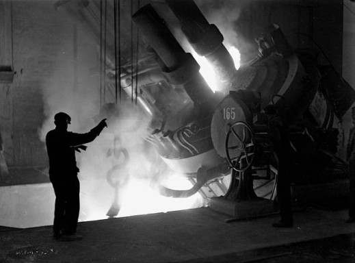 A black-and-white photograph of a worker standing beside a furnace directing the pouring of molten steel into a ladle.