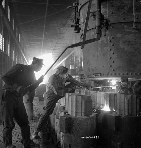 A black-and-white photograph of workers supervising the pouring of molten steel into moulds.