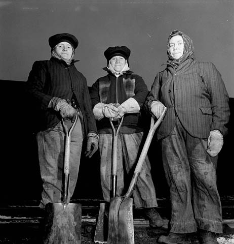 A black-and-white photograph of three women railroad workers wearing heavy work clothing and gloves while posing with their shovels.
