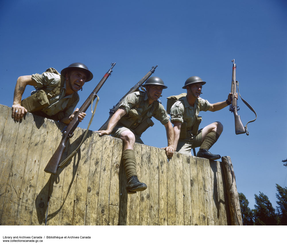 A colour photograph of three men climbing over a wooden fence clad in helmets, short-sleeved shirts, shorts, and socks and boots, and carrying rifles.