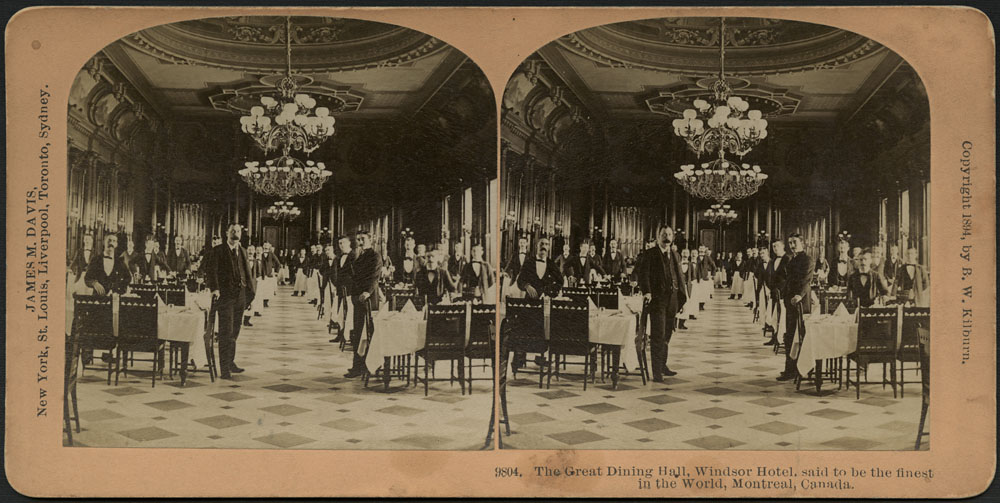 A black-and-white stereoscopic photograph of dozens of waiters standing at two rows of tables with chandeliers overhead, inside the Windsor Hotel, Montreal, Quebec.