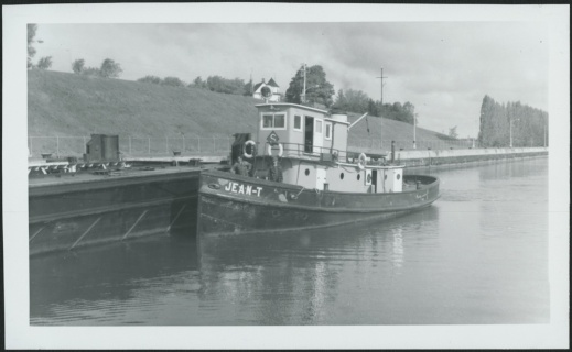 A black-and-white photograph of a moored tugboat. The crew is on the deck.