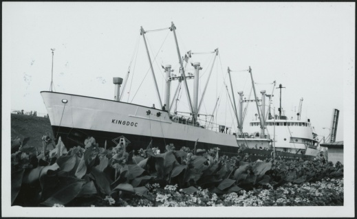 A black-and-white photograph of a large ship passing through the canal.