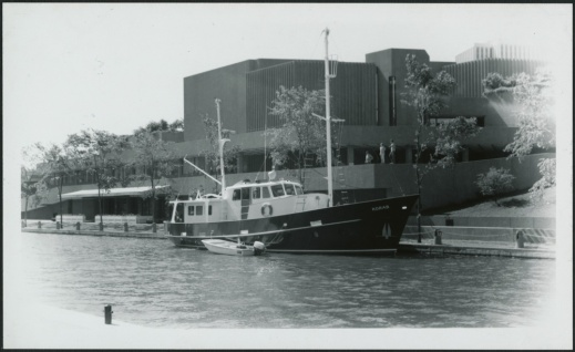 A black-and-white photograph of a moored leisure vessel on a canal beside a large building.