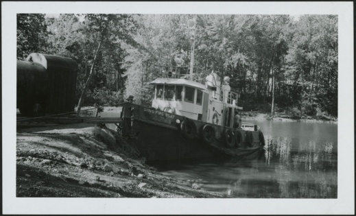 A black-and-white photograph of a small moored fire boat in a wooded stretch of waterway