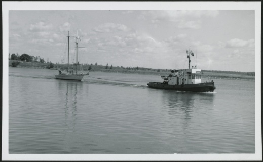 A black-and-white photograph of a tugboat towing a sailboat across the water.