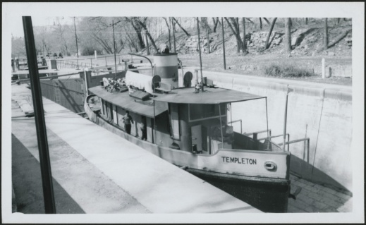 A black-and-white photograph of a medium-sized boat in the process of crossing a system of locks.