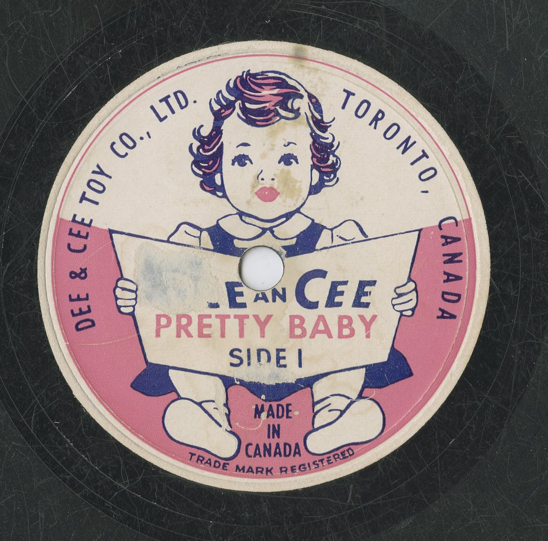 """A colour image of a record label for the Dee & Cee Toy Company, Ltd. Side 1 depicts a small girl sitting and holding an open book. The company name and the recording title """"Pretty Baby"""" are on the book cover."""