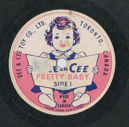 "A colour image of a record label for the Dee & Cee Toy Company, Ltd. Side 1 depicts a small girl sitting and holding an open book. The company name and the recording title ""Pretty Baby"" are on the book cover."