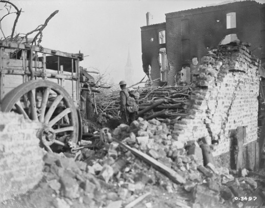A black-and-white photograph of a uniformed soldier, facing away from the camera and standing in the middle of the bricks and rubble of a destroyed building. A cart with a large wheel is on the left.