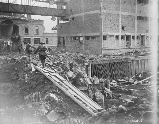 A black-and-white photograph of abandoned buildings, crumbling and filled with holes. The ground is covered in debris, mud, and rocks. Four soldiers are walking away from the camera, having crossed an expanse on a bridge made of debris.