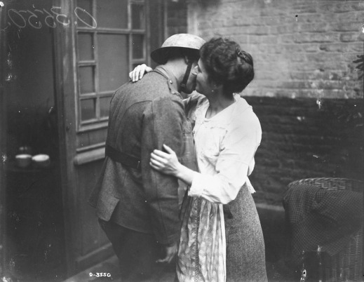 A black-and-white photograph of a woman in a white blouse with her arms around a soldier in uniform, kissing his cheek.