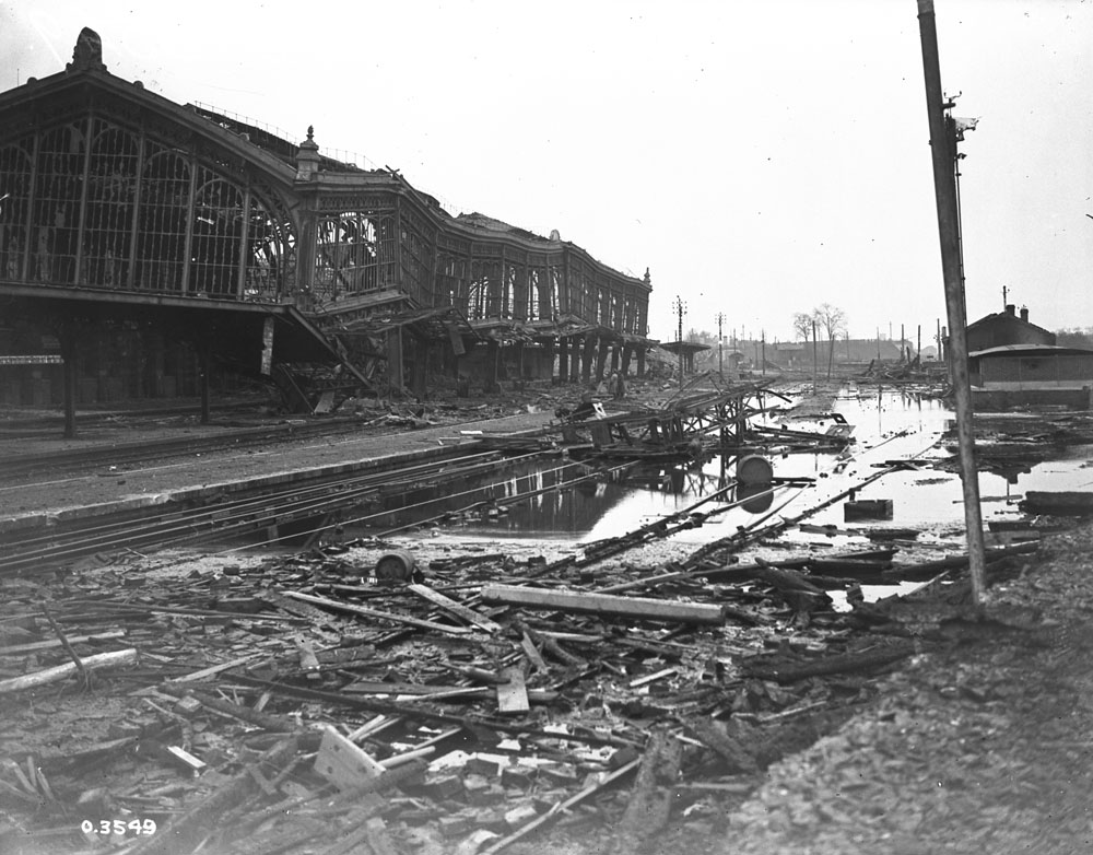 A black-and-white photograph of an ornate railway station in the background, crumpled and heaving, with broken windows and missing walls. The ground is cut diagonally with railway tracks, flooded with water, and littered with debris, planks of wood, and assorted rubble.