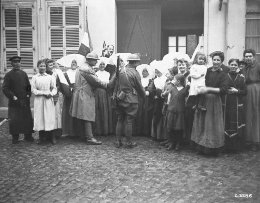 A black-and-white photograph of a group of people standing in front of a building with an open door. Women wearing wide white hats are shaking the hands of soldiers in uniforms. On both ends of the photograph, groups of civilian men and women are smiling into the camera. Someone in the back of the group is holding the French flag.