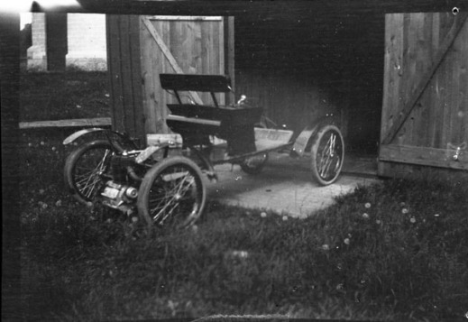 A black-and-white photograph of an early automobile parked outside of a barn.