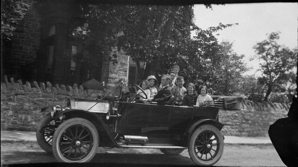 A black-and-white photograph of a man, a woman and six children in a convertible car parked in front of a house.
