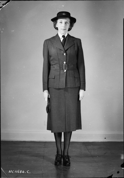 A black-and-white photograph of a woman standing straight to model a military uniform consisting of a Norfolk jacket, skirt, and black shoes.