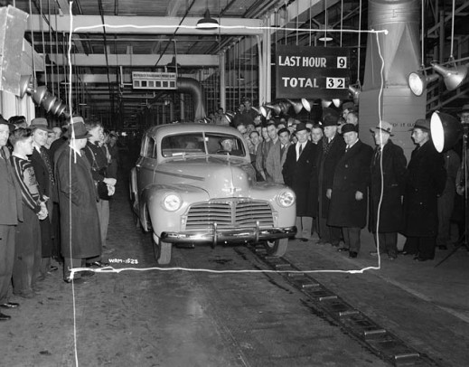 A black-and-white photograph of an automobile coming off the factory production line. There are groups of men on either side of the vehicle.