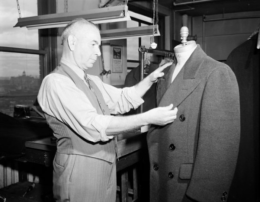 A black-and-white photograph of a tailor adjusting a suit jacket on a tailor's mannequin.