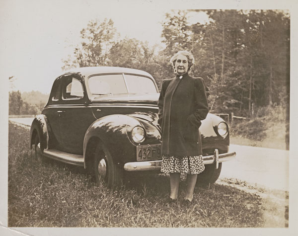 A black-and-white photograph of a woman wearing a coat and standing at the side of a road in front of her car.