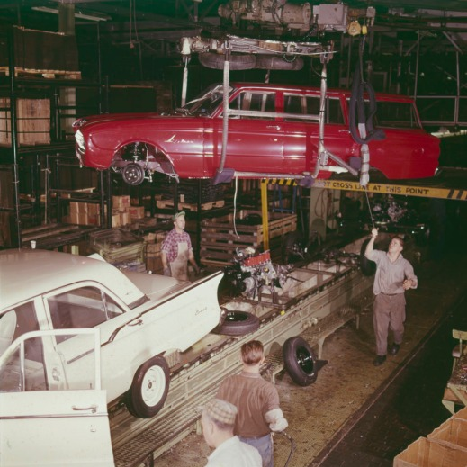 A colour photograph of two men guiding the frame of a red station wagon onto a moving production line.