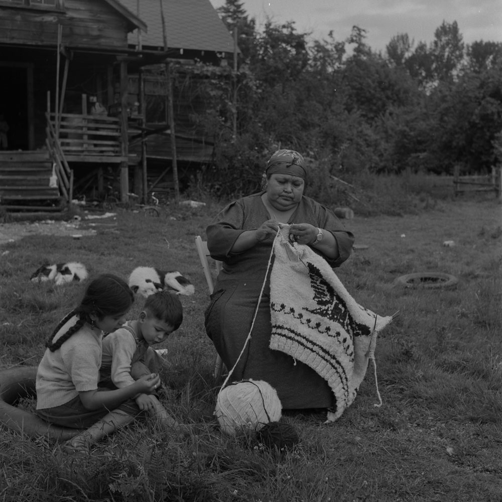 A black-and-white photograph of a woman sitting outside knitting a traditional Cowichan sweater. A boy and a girl sit next to her on the grass.