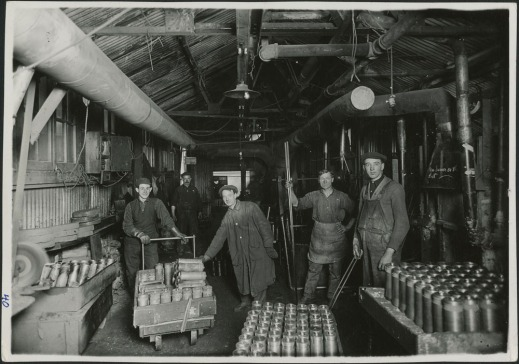 Black-and-white photograph of workers posing beside hundreds of shell cylinders.