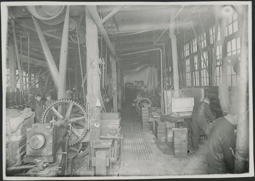 Black-and-white photograph showing the interior of a munitions and barbed-wire factory in 1916.