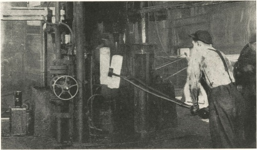Black-and-white photograph of a worker using long tongs on a glowing hot steel ingot.