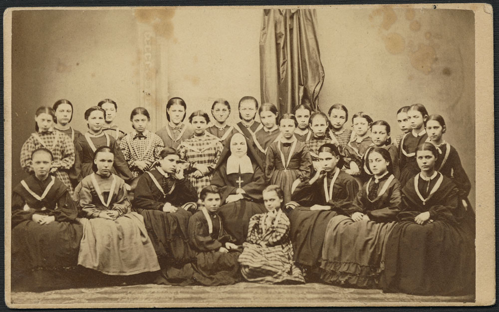 A black-and-white photographic portrait of 27 young girls wearing medals and seated around a nun.
