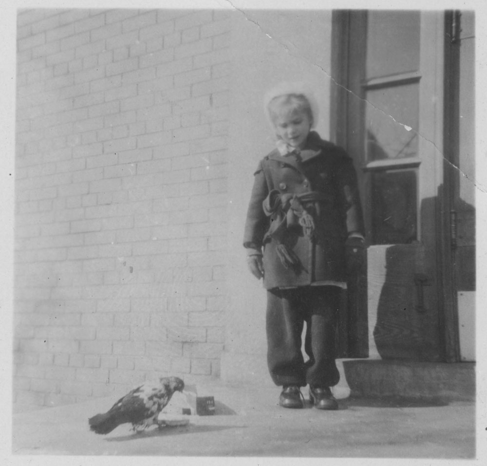 A black-and-white photograph of a little girl (Ann MacDonald) standing next to a door looking at a pigeon on the sidewalk.