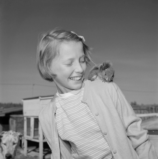 A black-and-white photograph of a girl and a squirrel on her left shoulder.