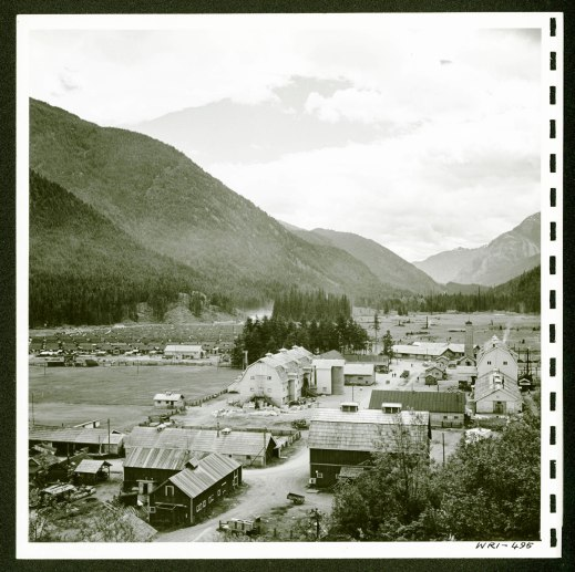 View of a small town surrounded by mountains. In the foreground are multiple buildings and in the background on the left are rows of smaller houses.