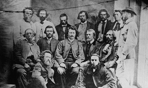 A black-and-white photograph of 14 men, arranged in three rows (the front two rows sitting and the back row standing), with Louis Riel seated in the centre.