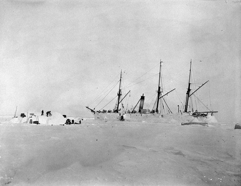 Black-and-white photo of a ship surrounded by snow and ice, with people next to it building a snow shelter.