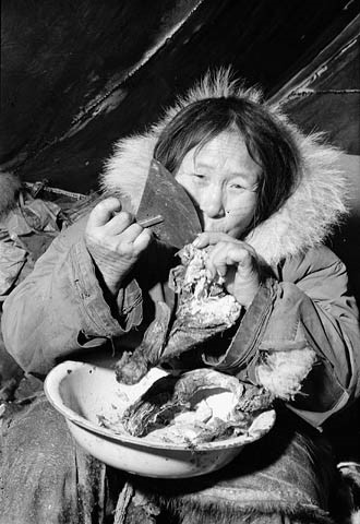 A black-and-white photo of an Inuk woman using her ulu to cut meat