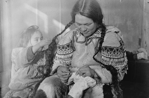 Black-and-white photo of a woman sewing skin boots, while a child plays with her braids.