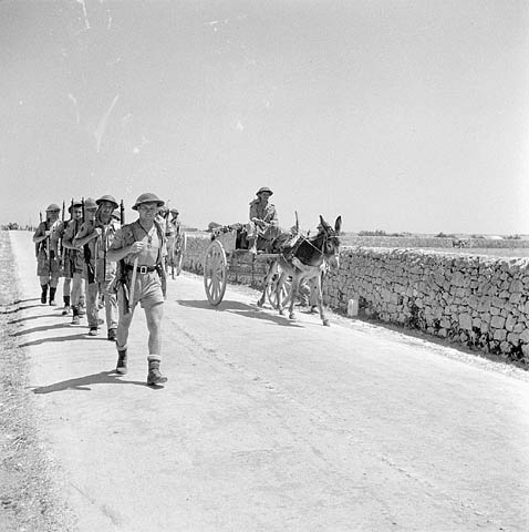 A black-and-white photograph of soldiers marching on a road. A soldier riding in a cart, pulled by a donkey, passes the group.